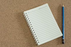 Notebook with pencil on cork board. Stock Image