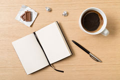 Notebook, pencil, cup of coffee and chocolate on wooden table Royalty Free Stock Photos