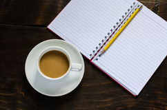 Notebook pencil and cup of coffee in wood table Royalty Free Stock Photos