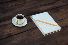 Notebook in pencil and cup of coffee on a wooden background. Notebook in a cell with a pencil and a cup of coffee on a wooden background Stock Photos