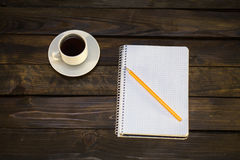 Notebook in pencil and cup of coffee on a wooden background. Notebook in a cell with a pencil and a cup of coffee on a wooden background Royalty Free Stock Photos