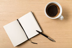 Notebook with pencil and cup of coffee on wooden table Stock Photo