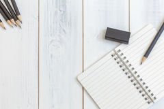 Notebook, pencil and eraser on wooden table, Top view, Concept of workplace, office supplies, background Royalty Free Stock Photo