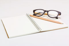 Notebook with a pencil and eye glasses Stock Images