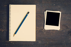 Notebook and pencil with frame photo on wood table background. With space stock photography