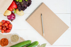 Notebook and pencil with fresh raw vegetables on wooden table. Top view of blank notebook and pencil with fresh raw vegetables on wooden table Stock Photos