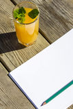 Notebook, pencil and glass orange juice Royalty Free Stock Photos