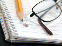 Notebook, pencil and glasses Stock Photo