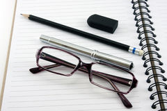 Notebook pencil glasses and eraser on white background Royalty Free Stock Photos