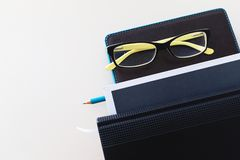 A notebook, a pencil, glasses and a stack of books, the business background to the concept of lifelong learning royalty free stock photography