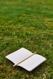 Notebook and pencil on the grass stock image