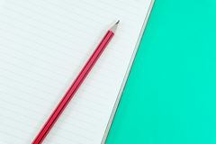 Notebook with pencil on green. Background Stock Photo