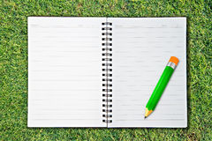 Notebook and pencil on Green Grass Stock Photo