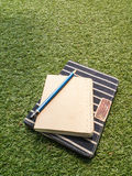 Notebook  and pencil on green grass Royalty Free Stock Photography