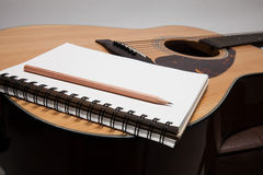 Notebook and pencil on guitar Stock Image