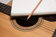 A notebook and pencil on guitar Stock Photo