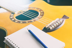 Notebook with pencil and guitar for songwriting. Blank notebook with pencil and guitar for songwriting Royalty Free Stock Images