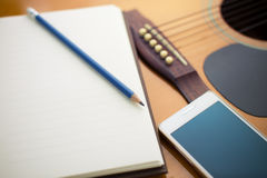 Notebook and pencil on guitar Stock Photos