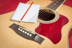 Notebook and pencil on guitar Royalty Free Stock Photos