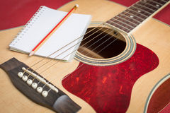 Notebook and pencil on guitar Royalty Free Stock Image