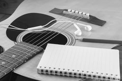 Notebook and pencil on guitar, Writing music , black and white Royalty Free Stock Images