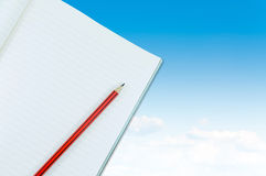 Notebook with pencil isolate on blue sky with clouds background Royalty Free Stock Photography