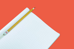 Notebook with pencil isolate on orange background Royalty Free Stock Images