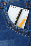 Notebook and pencil on jeans packet Royalty Free Stock Images