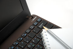 Notebook with pencil on laptop keyboard Stock Photo