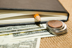 Notebook, pencil and money on the old tissue Royalty Free Stock Photos