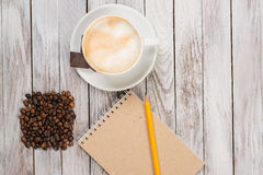 Notebook with a pencil next to coffee and coffee beans, piece of chocolate on white wooden background. Top view. Royalty Free Stock Photo