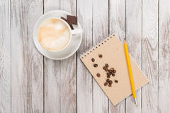 Notebook with a pencil next to coffee and coffee beans, piece of chocolate on white wooden background. Top view. Royalty Free Stock Image