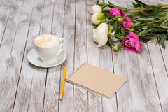 Notebook with a pencil next to coffee and peonies flowers on wooden background. Royalty Free Stock Photos
