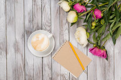 Notebook with a pencil next to coffee and peonies flowers on wooden background. Top view. Royalty Free Stock Images