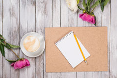 Notebook with a pencil next to coffee and peonies flowers on wooden background. Top view. Royalty Free Stock Photo