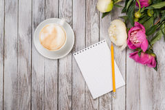 Notebook with a pencil next to coffee and peonies flowers on wooden background. Top view. Royalty Free Stock Photos