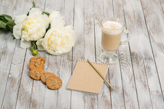 Notebook with a pencil next to glass of cappuccino and cookies on white wooden background. Place for text. Royalty Free Stock Images