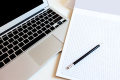 Notebook and pencil next to a laptop Royalty Free Stock Image