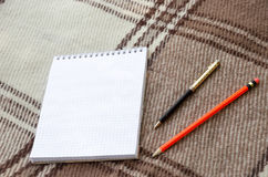 Notebook with pencil and notes on coverlet in flat lay. Notebook with pencil and notes on coverlet in flat lay Royalty Free Stock Photo