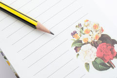 Notebook and pencil. Notebook pages with printed flowers Stock Photography