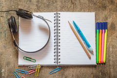 Notebook with pencil, pen, colored pens, headphone and paperclip Royalty Free Stock Photo