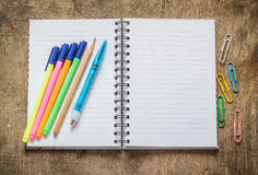 Notebook with pencil, pen, colored pens and paperclip Stock Image
