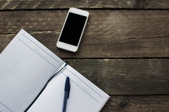 Notebook, pencil and phone on old wooden desk. Simple workspace Stock Photo