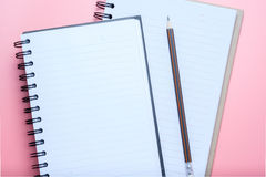 Notebook and pencil on pink background Stock Images