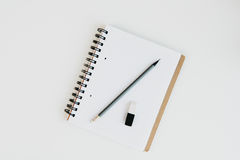 Notebook with pencil and rubber on table top Stock Images