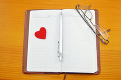 Notebook, pencil and a small red heart on a table Stock Photos