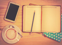 Notebook , pencil, smart phone and coffee cup with vinage filter Royalty Free Stock Photo