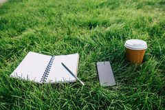 Notebook with pencil, smartphone with blank screen and disposable coffee cup on green lawn Royalty Free Stock Photography