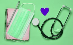 Notebook, pencil, stethoscope, decorative heart on a blue background. Medical equipment. Notebook, pencil, stethoscope, decorative heart on a blue background stock photo