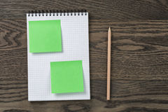 Notebook with pencil and sticky notes on oak wood table Royalty Free Stock Images